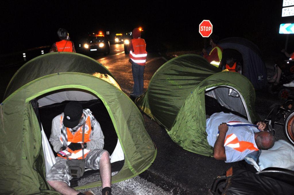 2 militantse nfauteuil sous les tentes au milieu de la chaussée