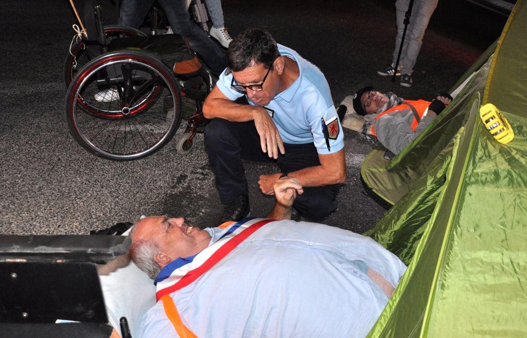 William Renault conseiller municipal de Lavaur au sol avec son écharpe tricolore échange avec un gendarme