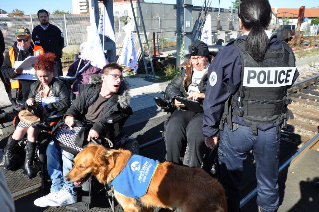 Plusieurs militants e nfauteuil ou avec handicap invisibles et des journalistes sur les rails en face du TGV qu'ils bloquent